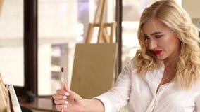 Muchacha rubia con los labios rojos con un cepillo en su mano en el estudio de dibujo almacen de metraje de vídeo