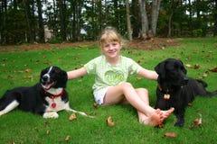 Muchacha rubia con los perros Foto de archivo libre de regalías