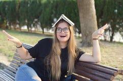 Muchacha rubia con los vidrios con un libro en su cabeza que se divierte al aire libre imágenes de archivo libres de regalías
