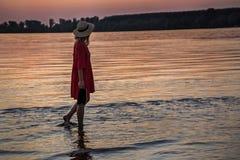 Muchacha rubia con un sombrero que camina por el río Imagen de archivo libre de regalías
