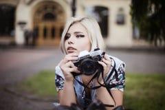 Muchacha rubia con una cámara del vintage que hace el selfie Foto de archivo