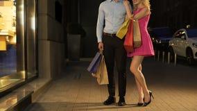 Muchacha rubia coqueta que abraza suavemente al hombre rico, disfrutando de compras costosas abundantes almacen de metraje de vídeo
