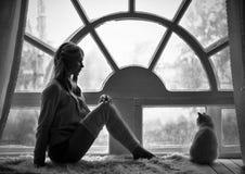 Muchacha rubia de la foto del arte y gato blanco que se sientan en la ventana vieja grande durante la lluvia Foto blanco y negro  fotos de archivo