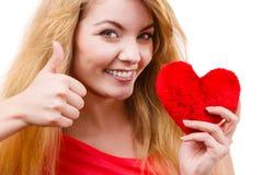 Muchacha rubia de la mujer que lleva a cabo símbolo rojo del amor del corazón Fotografía de archivo
