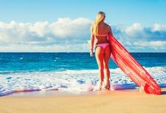 Muchacha rubia de la persona que practica surf en la playa Fotografía de archivo libre de regalías