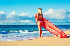 Muchacha rubia de la persona que practica surf en la playa Imagenes de archivo