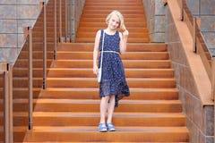 Muchacha rubia de moda en edad del preadolescente en un vestido que se coloca en una escalera oxidada elegante en un edificio mod Fotografía de archivo