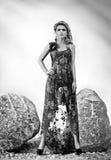 Muchacha rubia de moda en el vestido que presenta cerca de la roca Imágenes de archivo libres de regalías