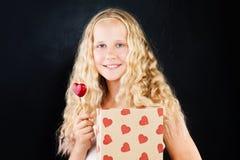 Muchacha rubia del adolescente con el corazón y el regalo rojos Imagen de archivo libre de regalías