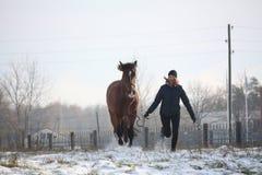 Muchacha rubia del adolescente y caballo marrón que corren en la nieve Fotografía de archivo libre de regalías