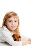 Muchacha rubia del cabrito con el mini perro de la mascota del animal doméstico del pinscher Imágenes de archivo libres de regalías