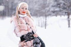 Muchacha rubia del día Nevado en un paseo en un parque del invierno Imagen de archivo libre de regalías