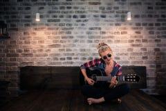 Muchacha rubia del encanto en la ropa causal que juega música en la guitarra imagen de archivo