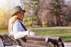 Muchacha rubia del estudiante con el sombrero en el banco de parque que trabaja en el ordenador portátil imagen de archivo