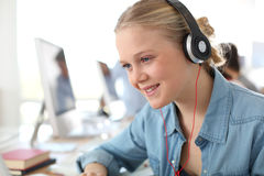 Muchacha rubia del estudiante con los auriculares en clase Foto de archivo libre de regalías