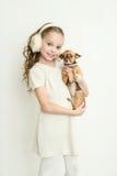 Muchacha rubia del niño con el pequeño perro casero Imágenes de archivo libres de regalías