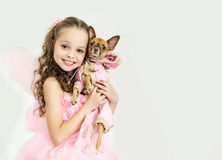 Muchacha rubia del niño con el pequeño perro casero Foto de archivo libre de regalías