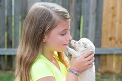 Muchacha rubia del niño con jugar de la chihuahua del animal doméstico del perrito Foto de archivo libre de regalías