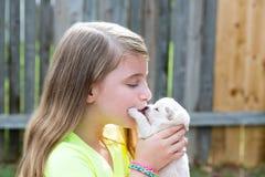 Muchacha rubia del niño con jugar de la chihuahua del animal doméstico del perrito Imagen de archivo libre de regalías