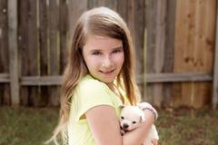 Muchacha rubia del niño con jugar de la chihuahua del animal doméstico del perrito Fotografía de archivo libre de regalías