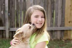 Muchacha rubia del niño con jugar del perro casero de la chihuahua Imagen de archivo