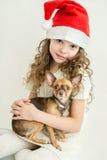 Muchacha rubia del niño en el sombrero de Santa Claus con el pequeño perro casero Fotos de archivo libres de regalías