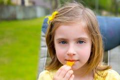Muchacha rubia del niño que come los bocados del maíz en parque al aire libre Imagenes de archivo