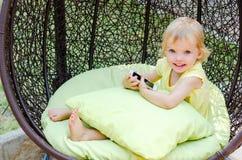 Muchacha rubia del niño que juega con el smartphone que se sienta en silla de mimbre Imágenes de archivo libres de regalías