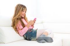 Muchacha rubia del niño que juega la diversión con el teléfono móvil en el sofá blanco Fotografía de archivo
