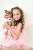 Muchacha rubia del niño con el pequeño perro casero Fotografía de archivo libre de regalías