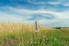 Muchacha rubia del preescolar del niño que va abajo del camino de tierra entre campo de grano Fotografía de archivo libre de regalías