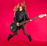 Muchacha rubia del rock-and-roll con salto de la guitarra baja en rojo Imágenes de archivo libres de regalías
