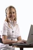 Muchacha rubia del servicio de atención al cliente que trabaja en la computadora portátil fotos de archivo