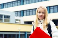 Muchacha rubia delante de la construcción de escuelas fotos de archivo libres de regalías