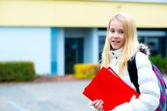 Muchacha rubia delante de la construcción de escuelas Imagen de archivo libre de regalías