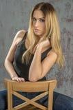 Muchacha rubia delgada joven en vaqueros y camisa que presenta coqueto Fotografía de archivo libre de regalías