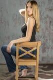 Muchacha rubia delgada joven en vaqueros y camisa que presenta coqueto Imagen de archivo