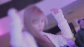 Muchacha rubia elegante caliente que baila a la música en el partido, manos que agitan almacen de metraje de vídeo
