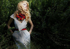 Muchacha rubia en arbustos verdes Fotos de archivo