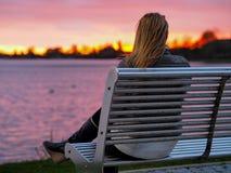 Muchacha rubia en banco que disfruta de puesta del sol fotografía de archivo