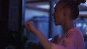 Muchacha rubia en el baile rosado de la chaqueta en el sofá en partido en club nocturno holidays metrajes