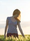 Muchacha rubia en el campo verde que disfruta de la naturaleza en verano Foto de archivo libre de regalías