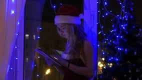 Muchacha rubia en el sombrero de santa con una tableta metrajes