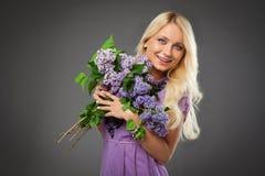 Muchacha rubia en el vestido púrpura que sostiene el ramo de la lila o Imagenes de archivo