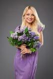 Muchacha rubia en el vestido púrpura que sostiene el ramo de lila Fotografía de archivo libre de regalías