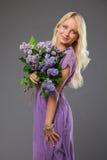 Muchacha rubia en el vestido púrpura que sostiene el ramo de lila Imagen de archivo libre de regalías