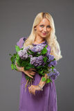 Muchacha rubia en el vestido púrpura que sostiene el ramo de lila Foto de archivo