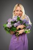 Muchacha rubia en el vestido púrpura que sostiene el ramo de lila Imagenes de archivo