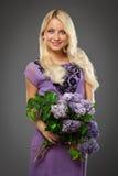 Muchacha rubia en el vestido púrpura que sostiene el ramo de lila Imágenes de archivo libres de regalías