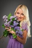 Muchacha rubia en el vestido púrpura que sostiene el ramo de lila foto de archivo libre de regalías